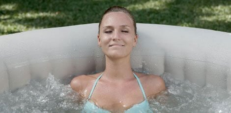 Lady taking bubble bath in lay z spa inflatable hot tub